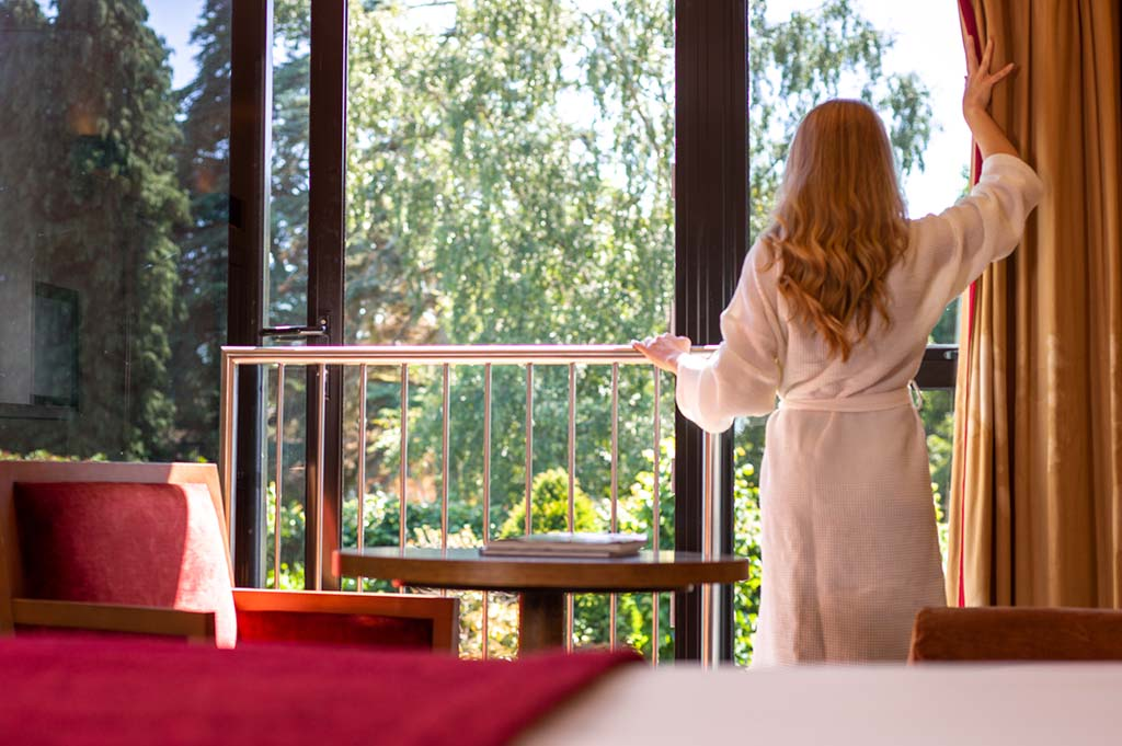 Woman opening the curtains to look out the window of her garden view bedroom