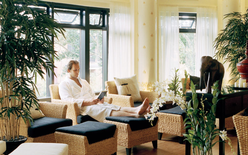 Man sitting down reading a book in the Thai relaxation room at SenSpa.
