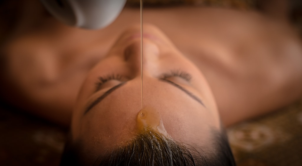 Honey being poured onto a woman's head as part of her spa facial.
