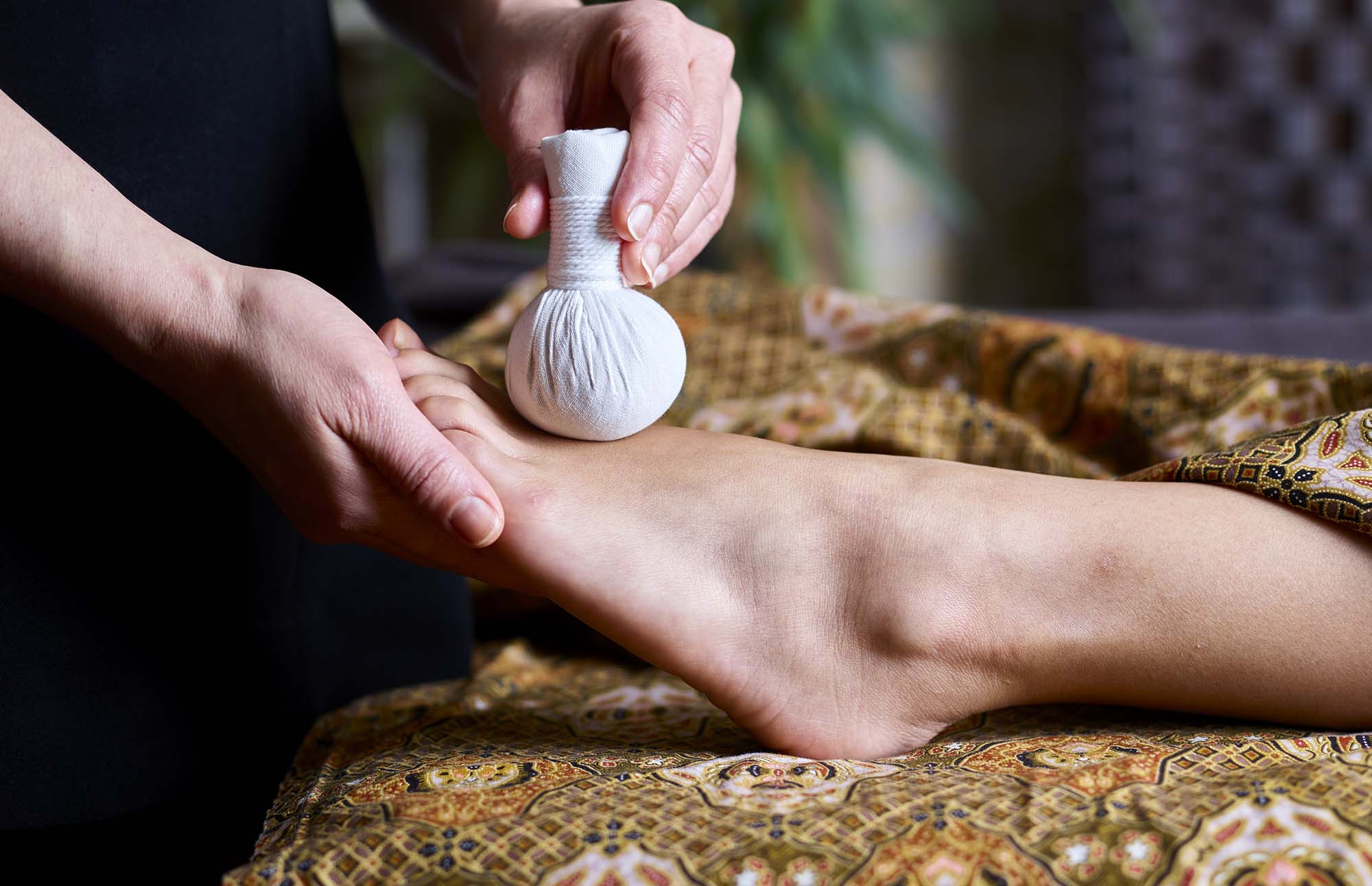 The therapist is using a Thai poultice to massage a woman's foot