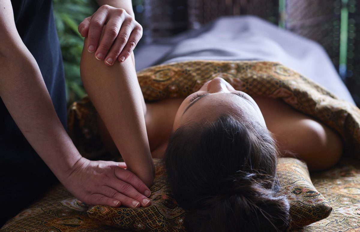 Therapist manipulates woman's arm as part of the SenFusion massage
