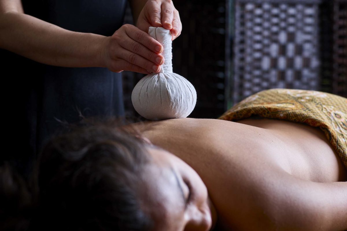 Therapist uses Thai poultice to massage woman's back