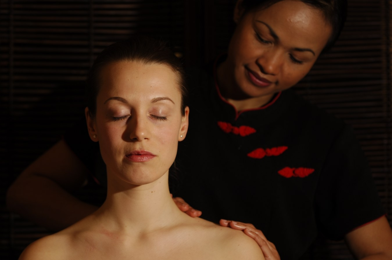 Thai Therapist is massaging a woman's shoulder