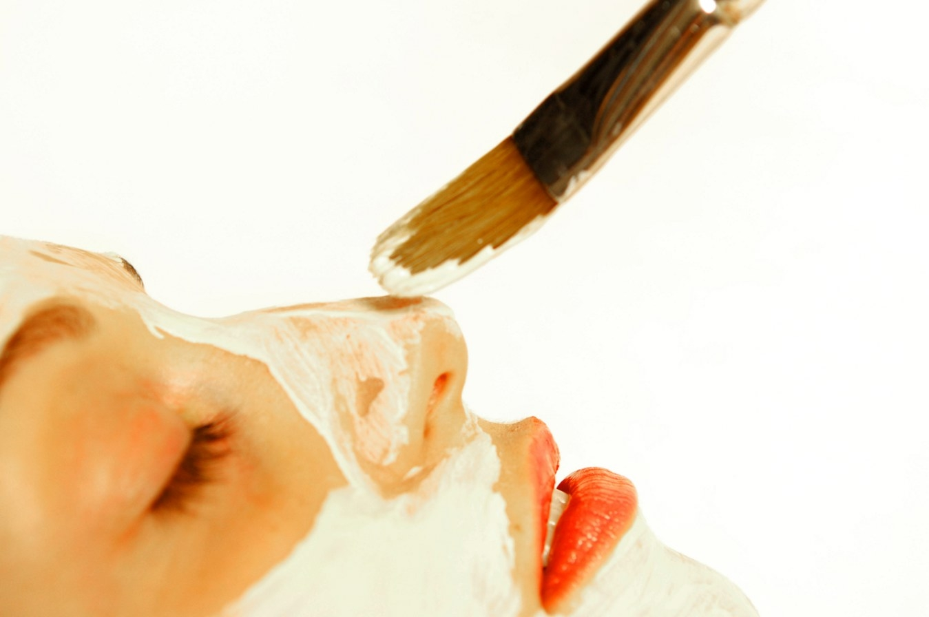 Product being painted on to a woman's face as part of her spa facial