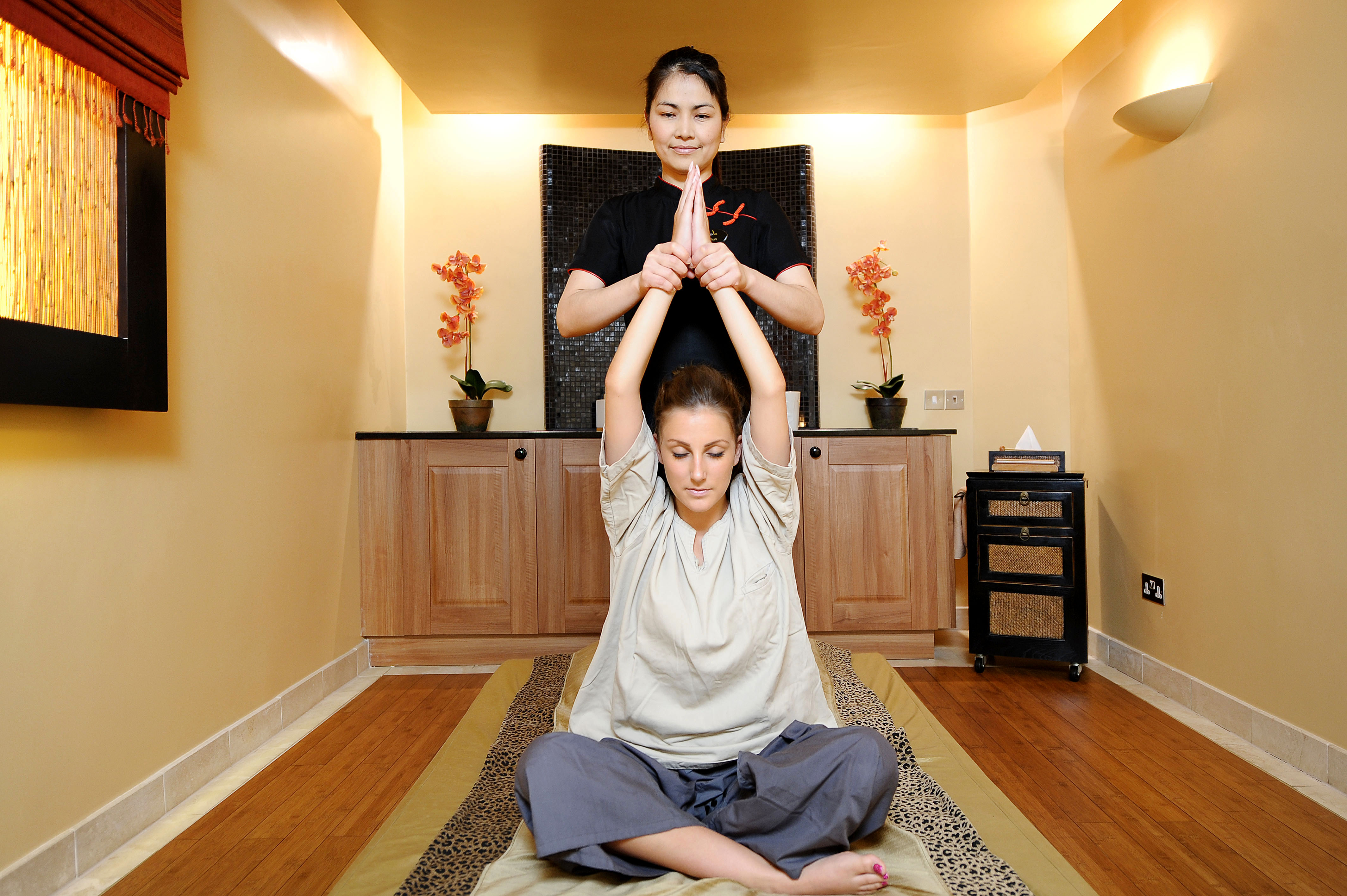 Thai therapist holding woman's arms above her head during a traditional Thai massage.