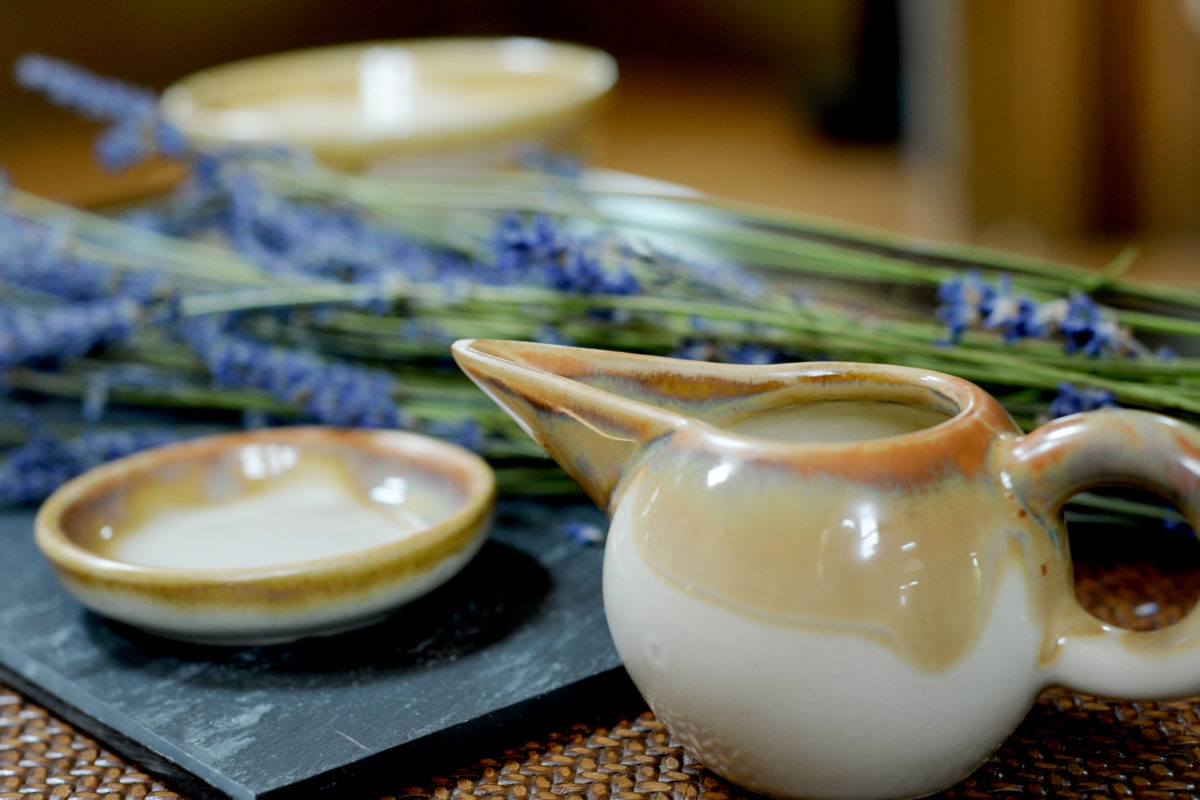 A pot of oil and lavender are placed on a tray ready for spa treatments.