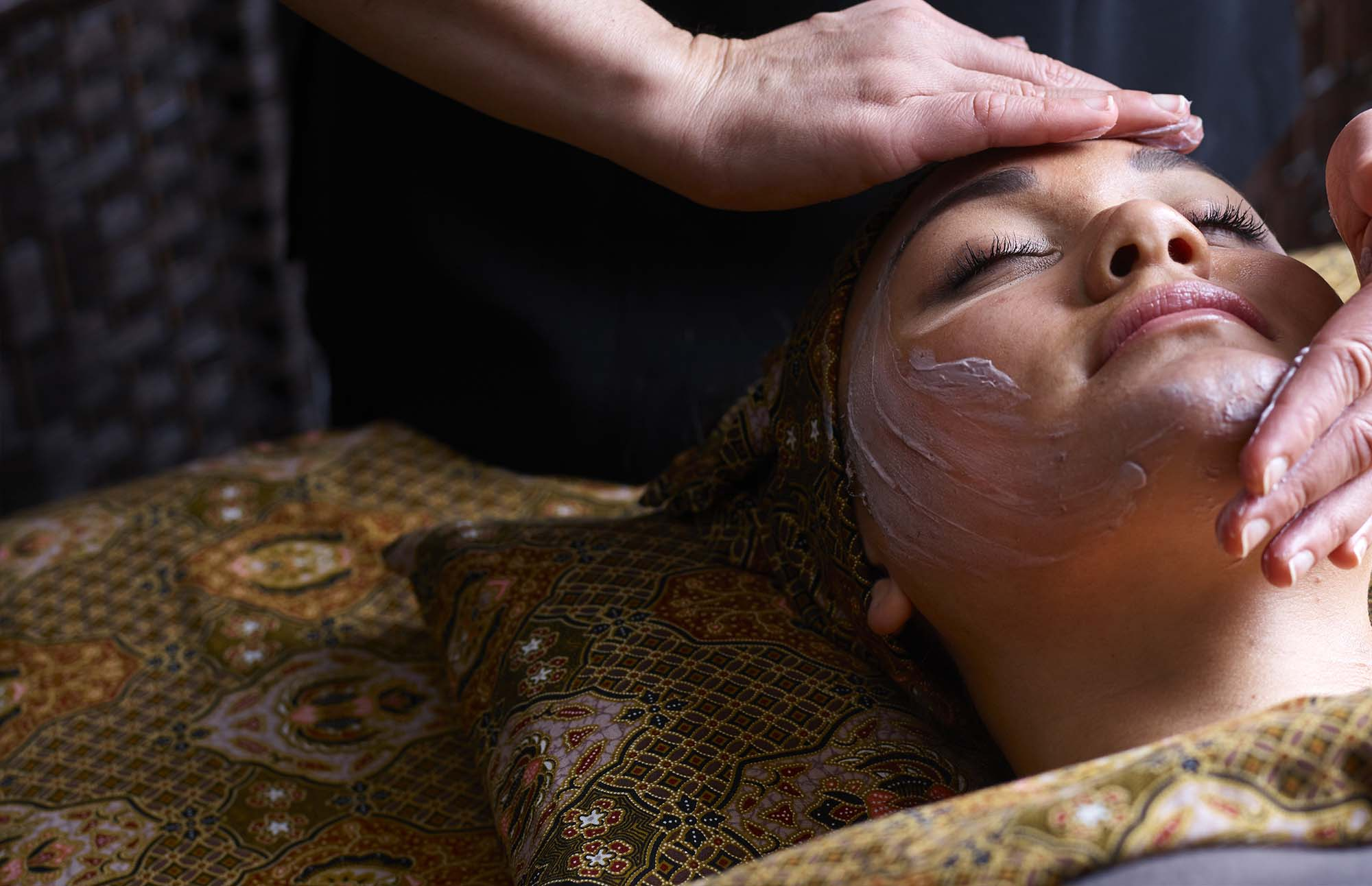 Therapist applying spa skin care products to woman's face