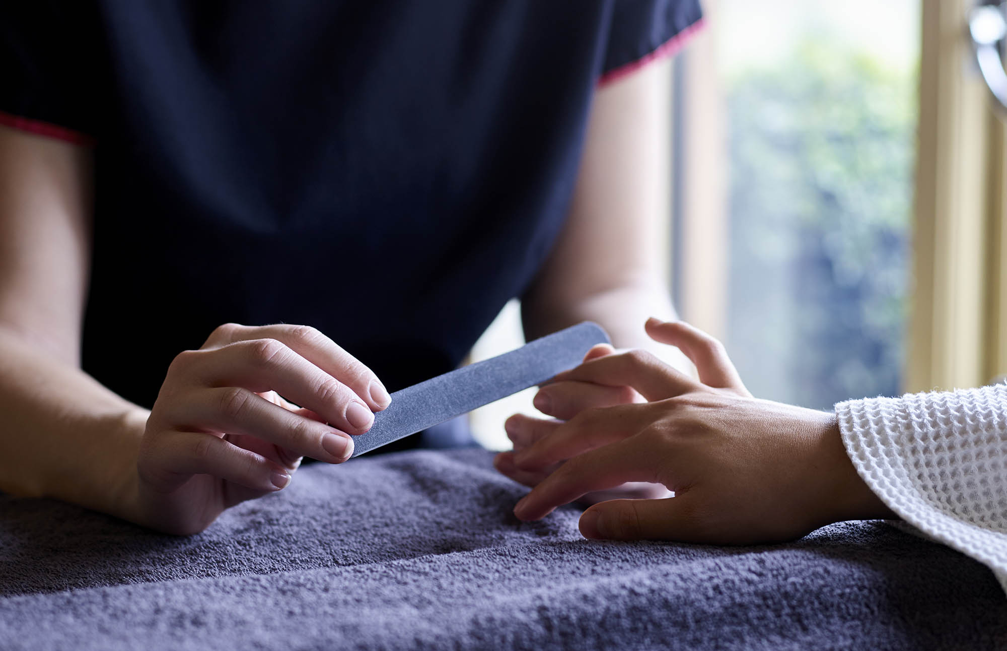 Therapist files woman's finger nails