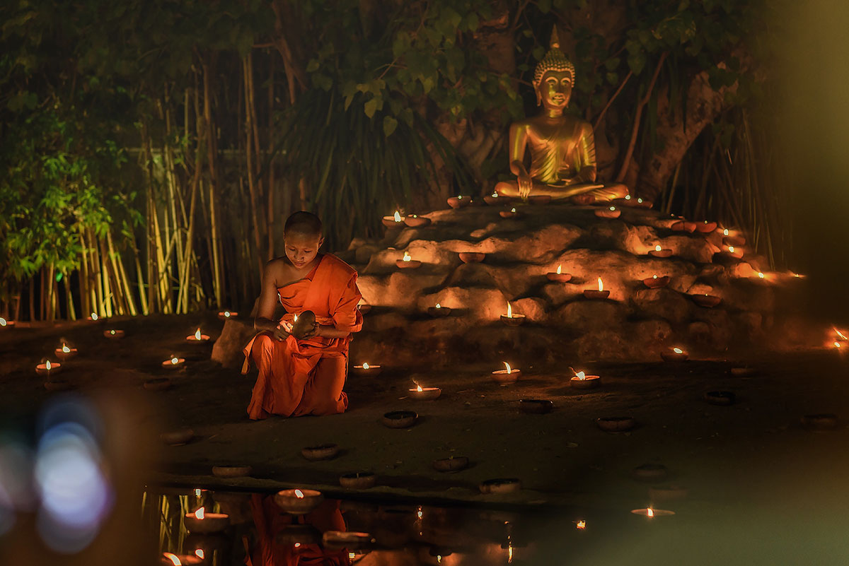 A Thai man lights the candle in his Krathong ready to place it in the river