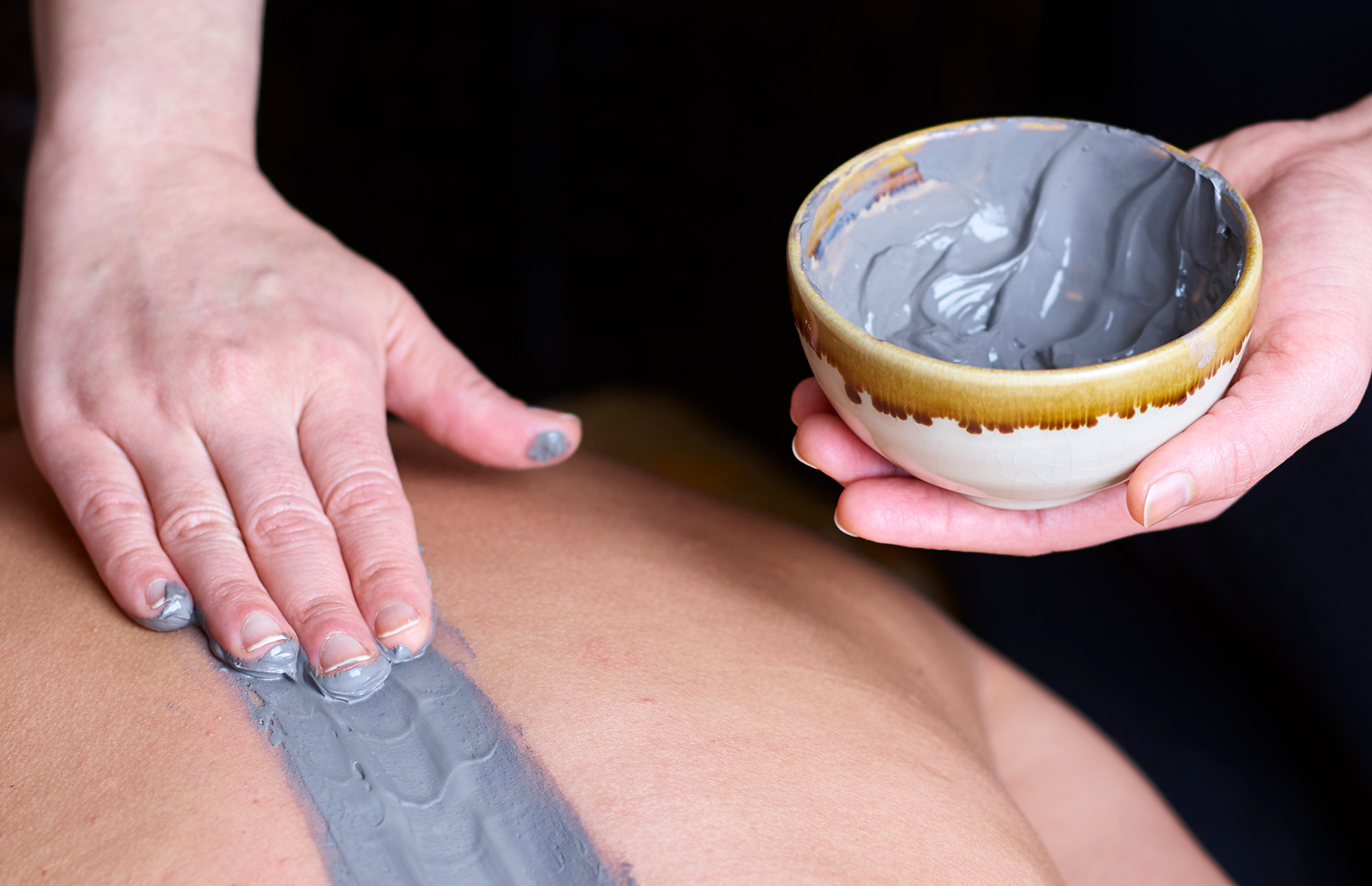 Therapist applying product using hand to woman's back