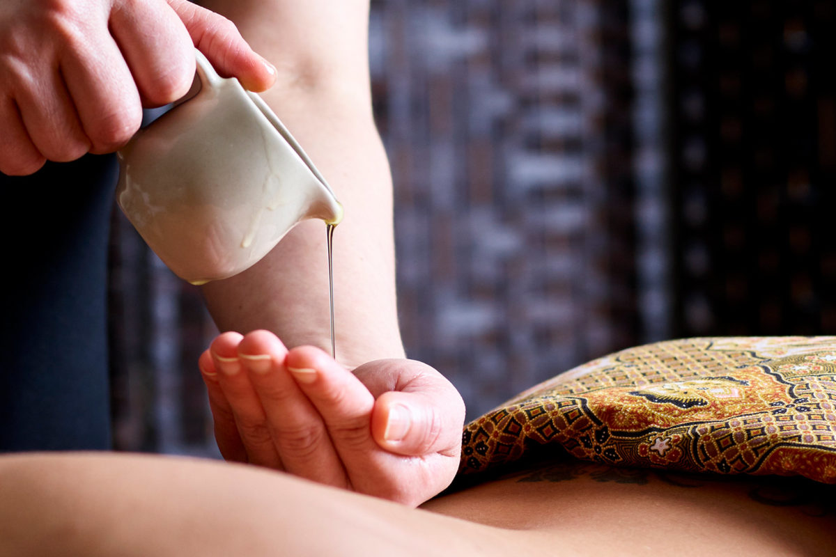 Therapist pours oil onto her hand ready to apply to woman's back for a massage.