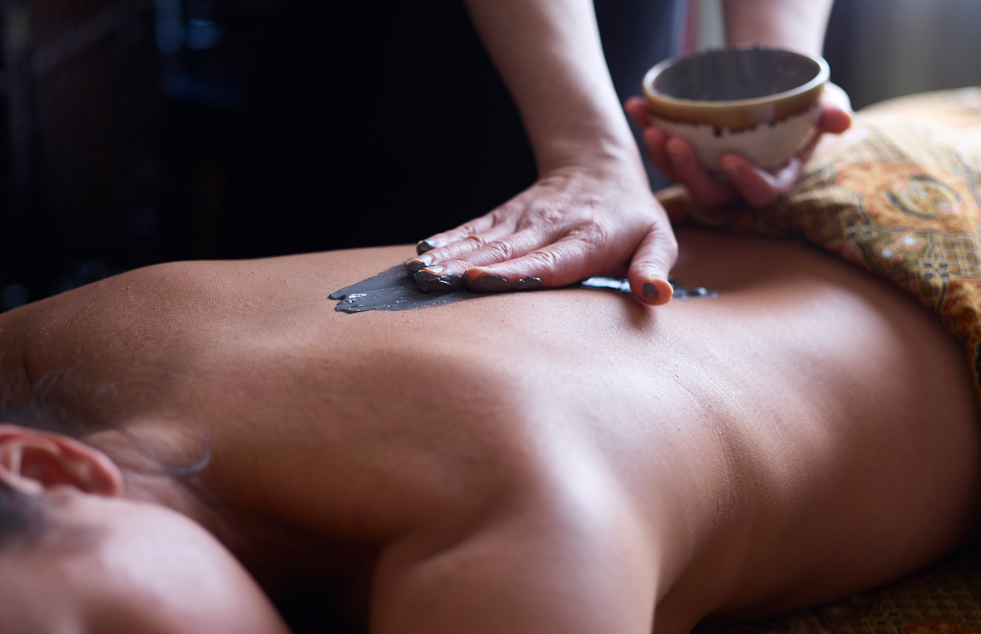 A therapist applies a mud treatment using her hand to a woman's back.