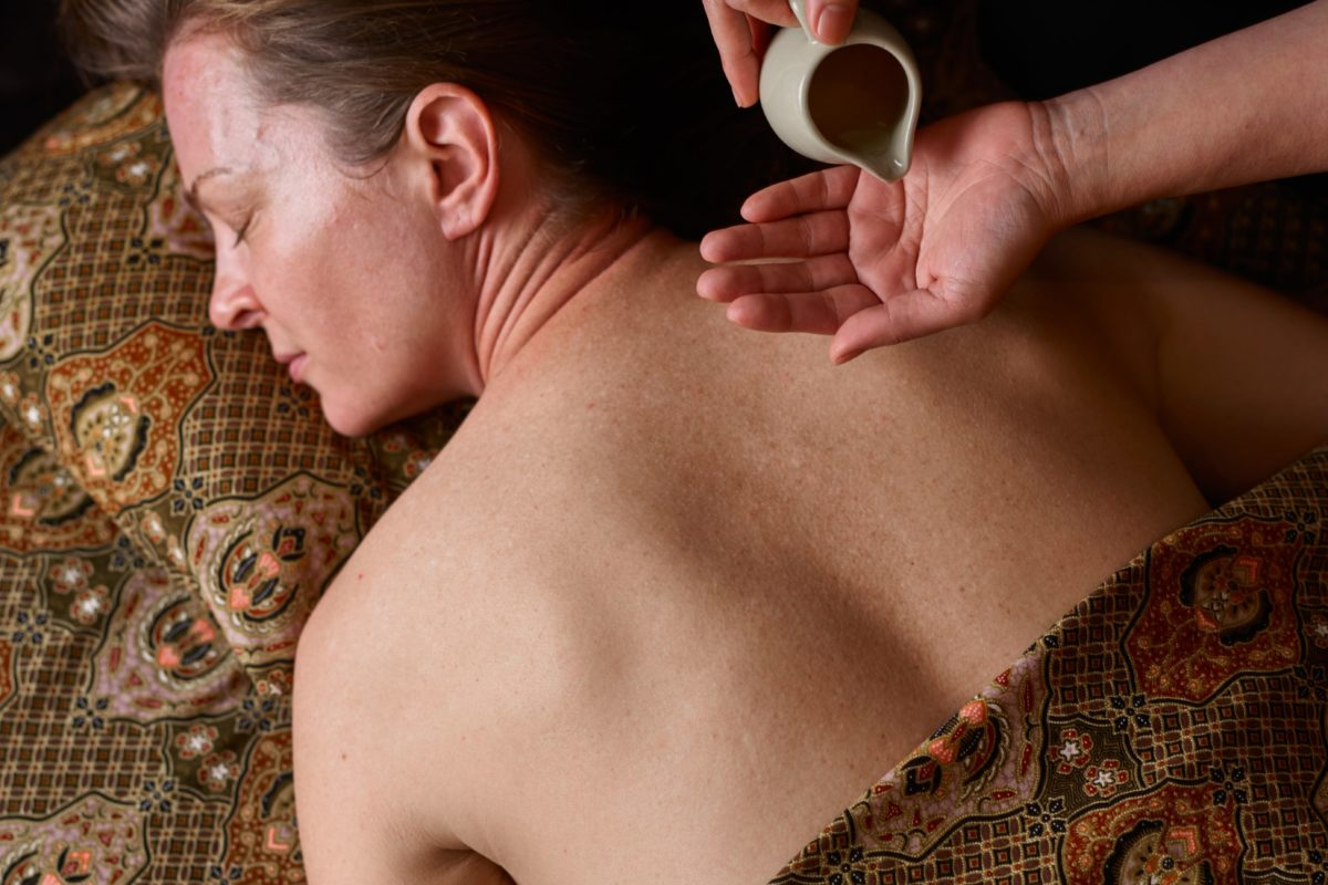 Therapist pours oil in to her hand for a massage