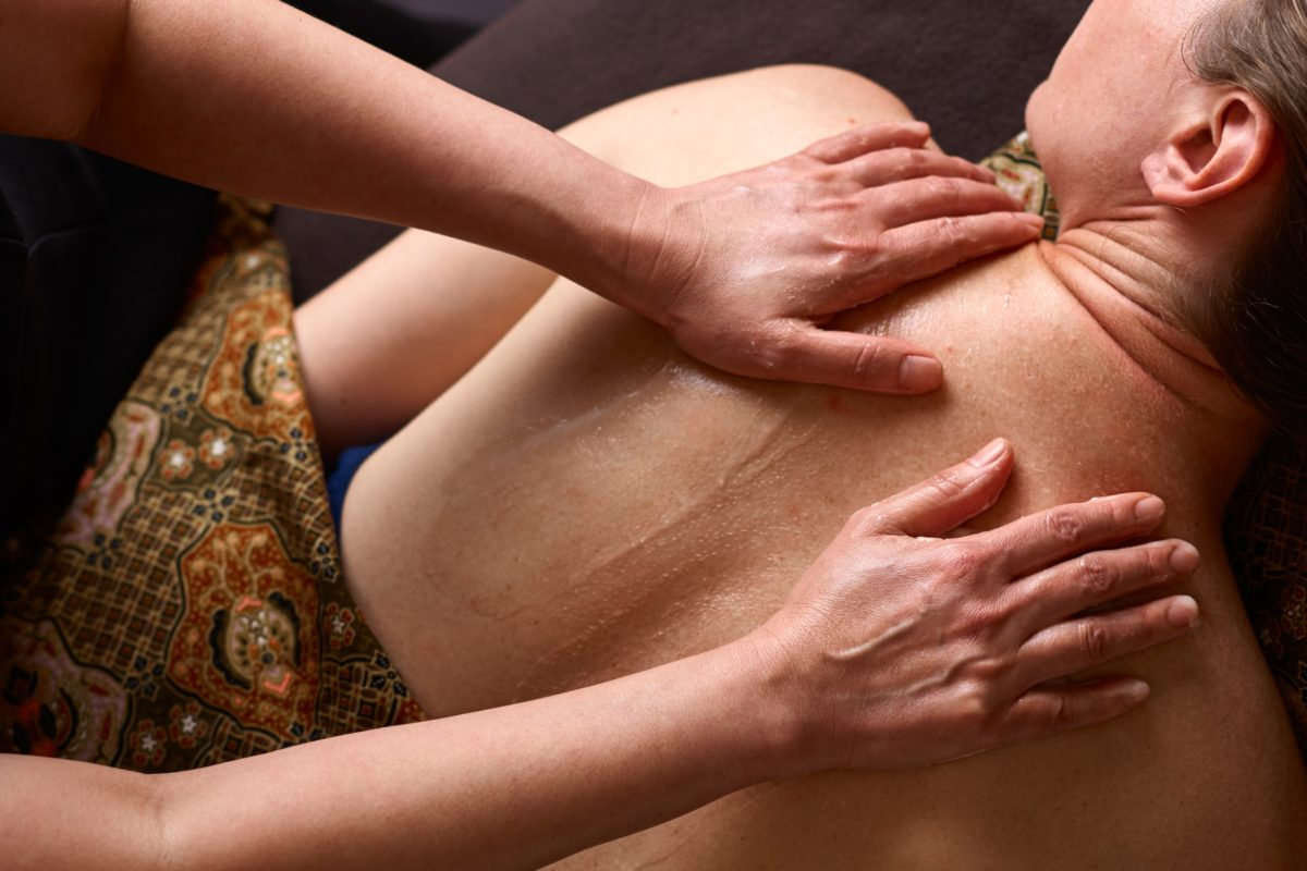 Therapist massaging spa products in to woman's back