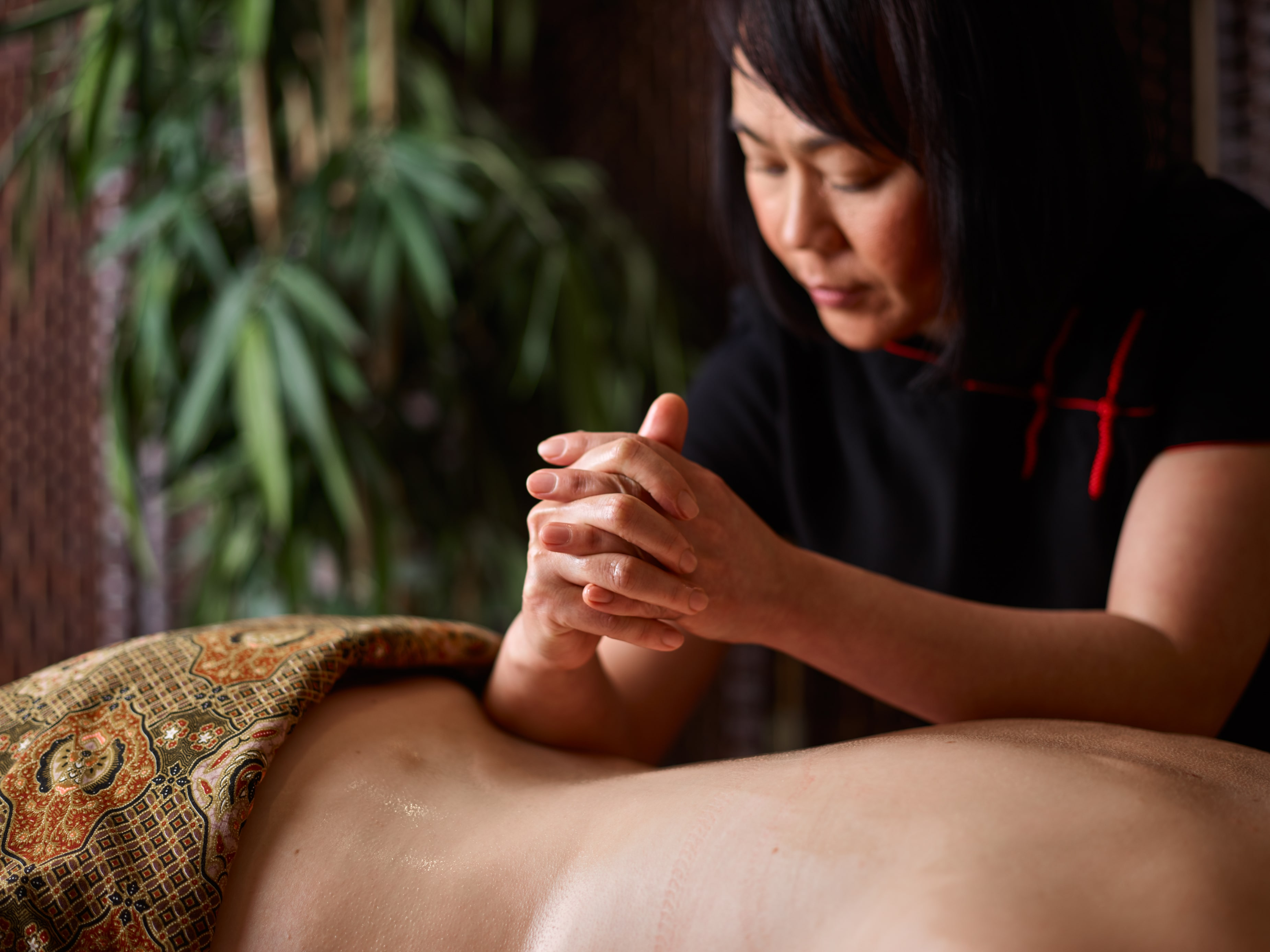 Therapist is using her forearms to massage a woman's back
