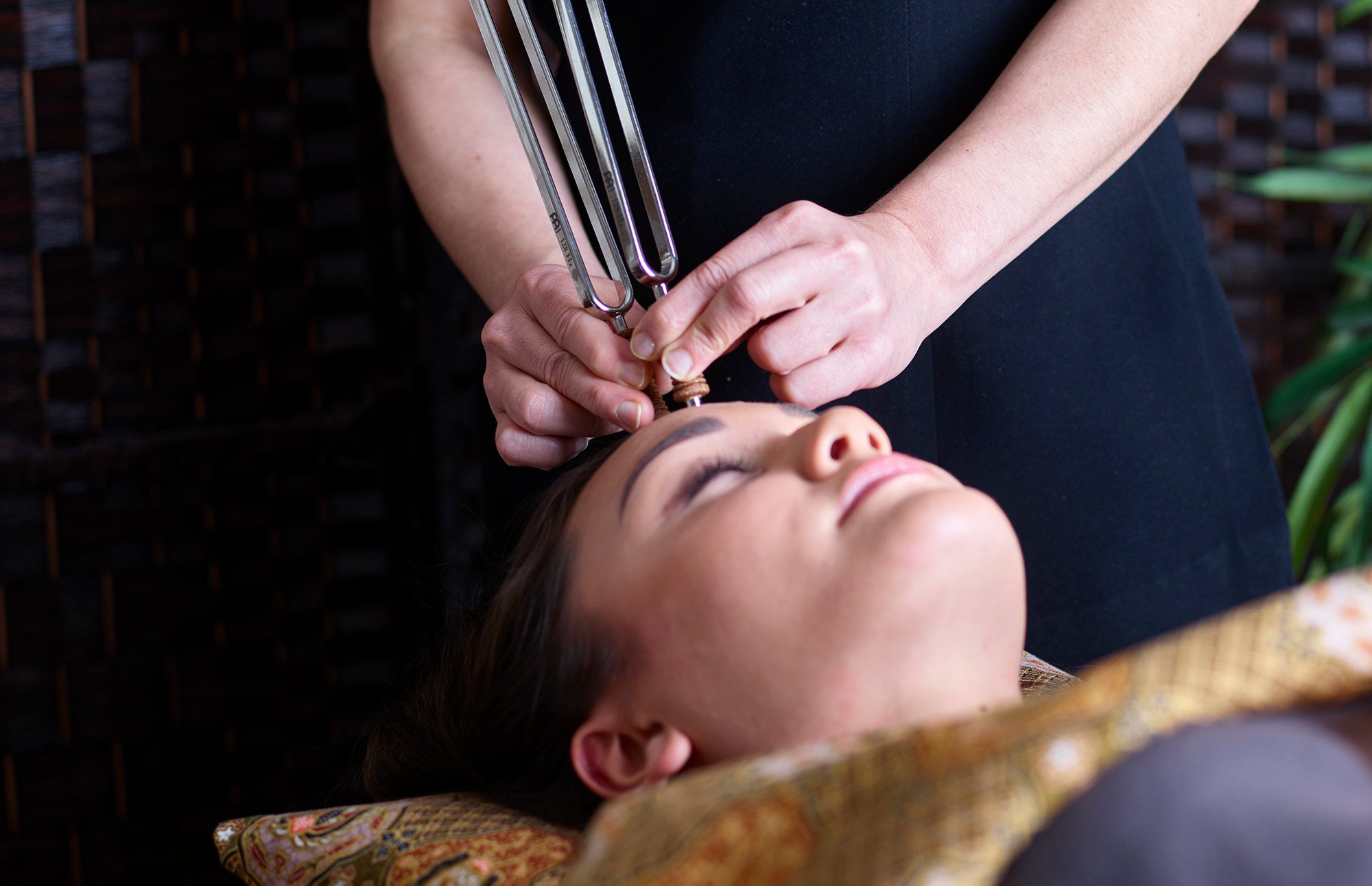 Therapist holding tuning forks to a woman's head as part of the SKN-RG wave facial