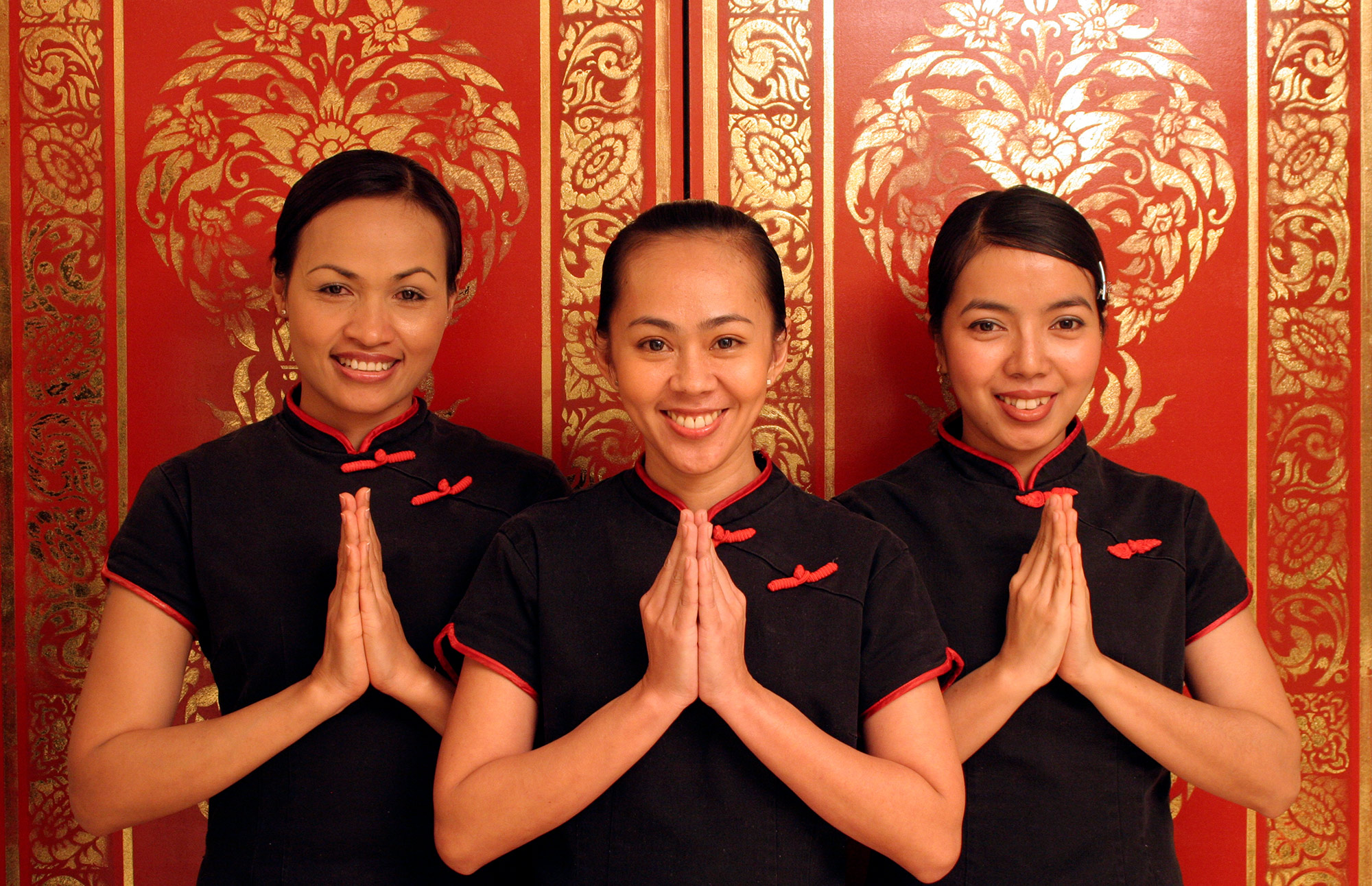 Three Thai therapists with their hands in meditation position, standing in front of an ornate door