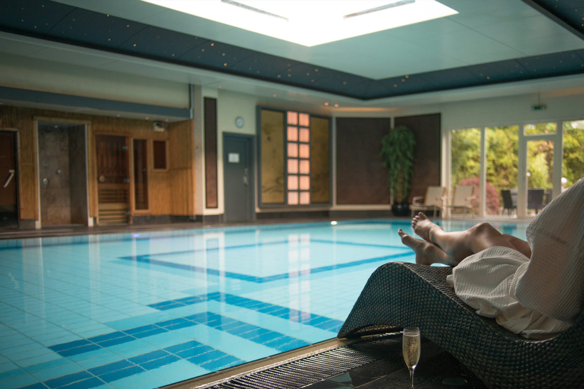 Woman relaxing by the pool with a glass of champagne.
