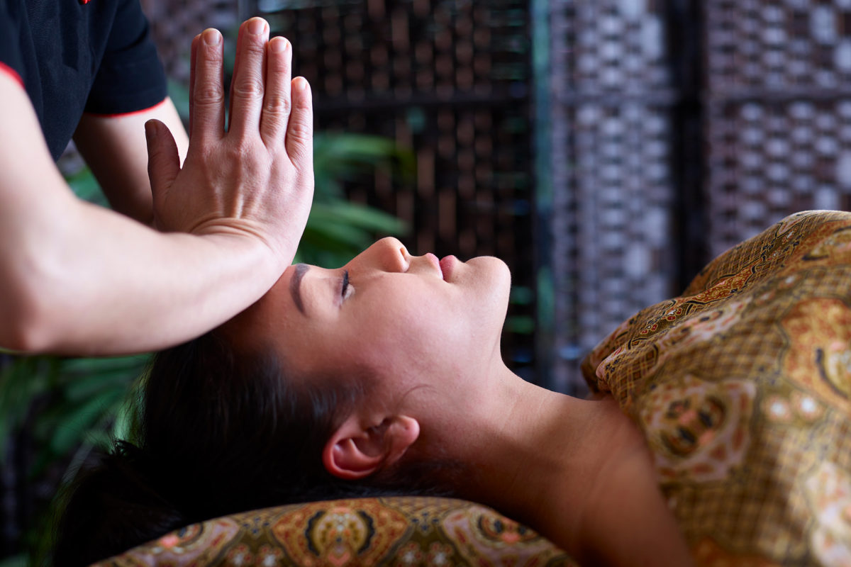 Thai therapist with hands in meditative position over woman's head as she lays ready for her SenSpa treatment