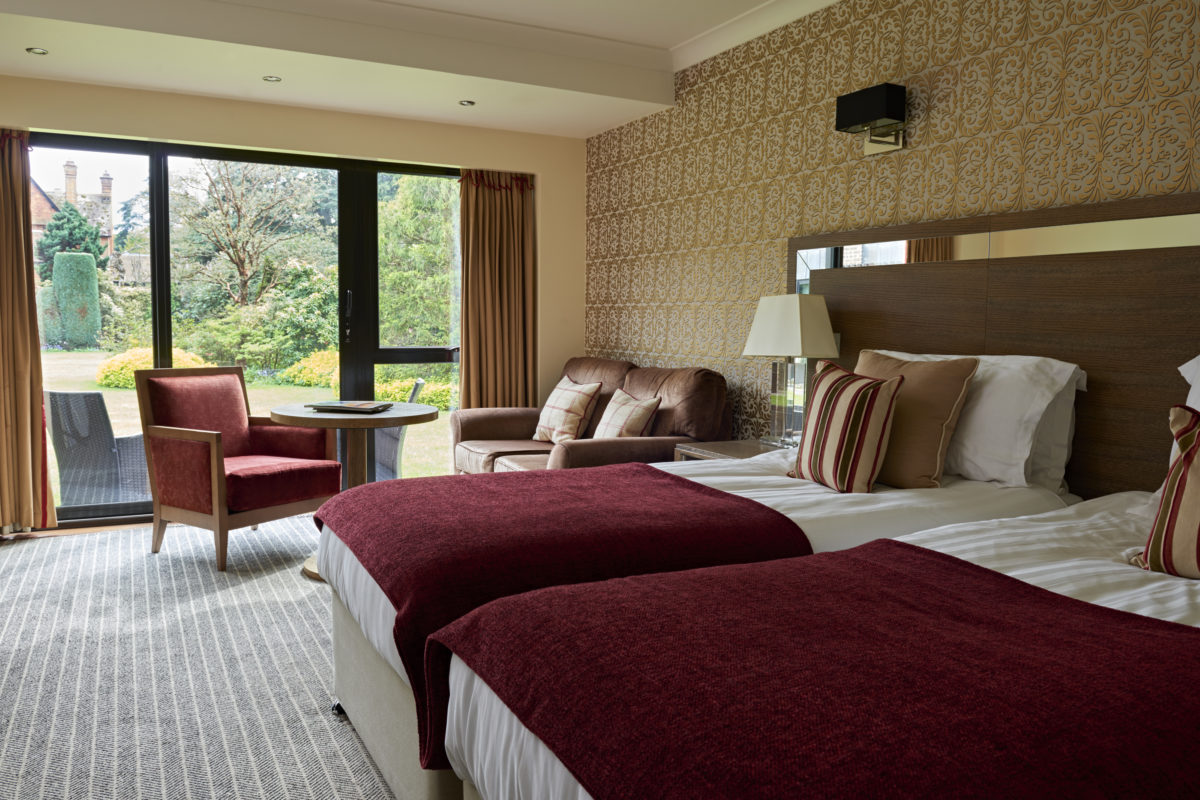 Bedroom at Careys Manor with view garden view and patio