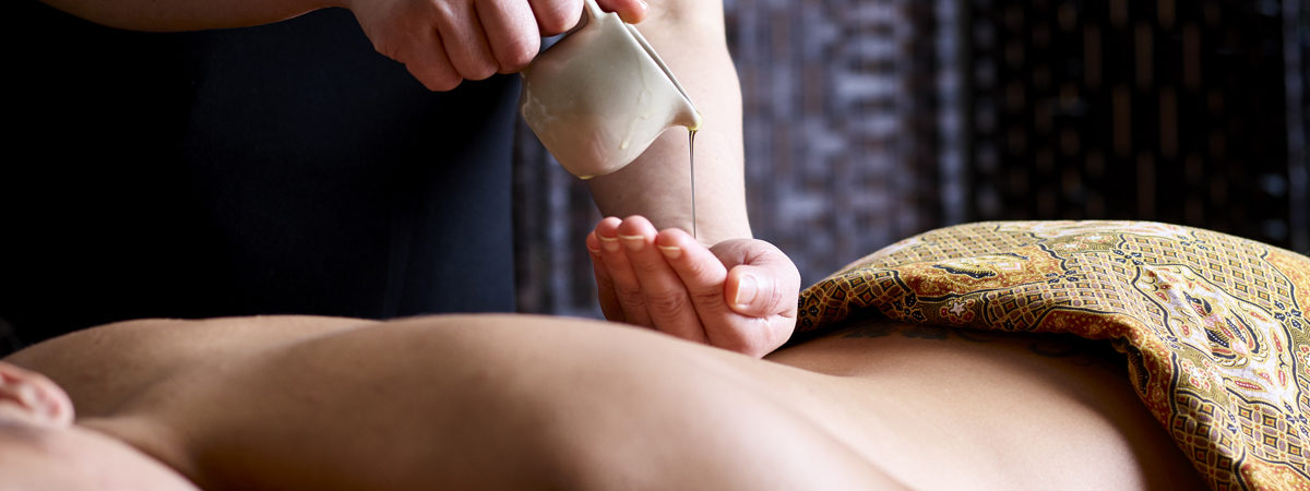 Woman pouring massage oil onto a back